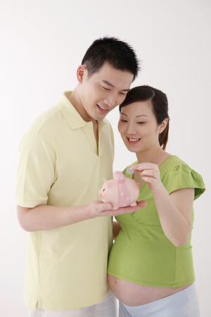 two people fertility: Pregnant woman putting coin into piggy bank, man holding the piggy bank
