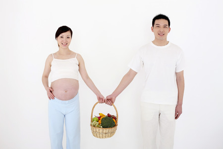 two people fertility: Pregnant woman and man holding a basket of fruits and vegetables