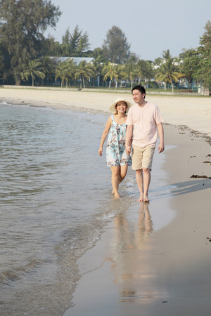 holding hands while walking: Man and woman holding hands while walking along the beach LANG_EVOIMAGES