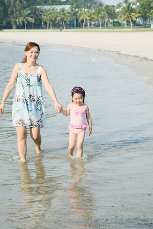 holding hands while walking: Mother and daughter holding hands while walking along the beach