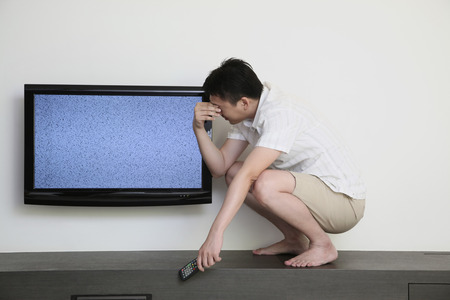 squatting: Man squatting beside a ruined television with hand on head