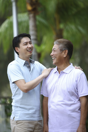 pat: Man giving his father a pat on the shoulder while talking  LANG_EVOIMAGES
