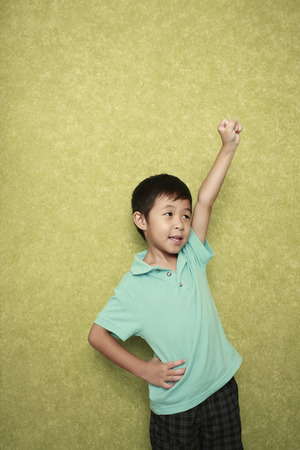 arm raised: Boy standing at the wall with his arm raised