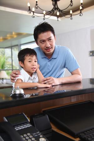 hotel reception: Vater und Sohn warten an der Hotelrezeption