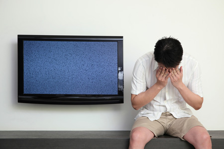 Man sitting next to a ruined television crying