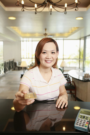 hotel reception: Frau h�lt Kreditkarte an der Hotelrezeption LANG_EVOIMAGES