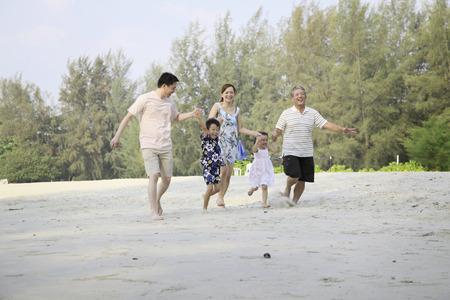 family one: Una famiglia felice camminare mano nella mano sulla spiaggia