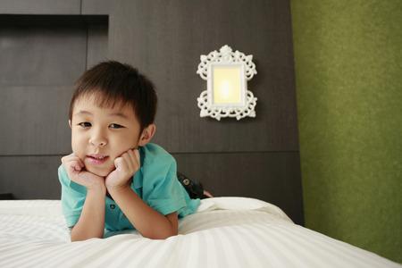 lying forward: Boy lying forward in bed LANG_EVOIMAGES