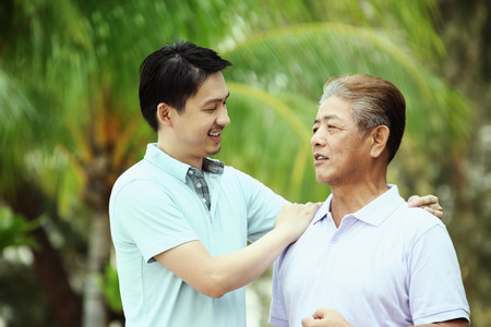 one parent: Man giving his father a pat on the shoulder while talking  LANG_EVOIMAGES