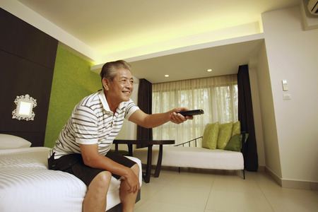 changing channel: Man changing the channel with a remote control