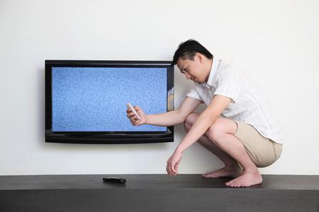 cuclillas: El hombre en cuclillas al lado de un televisor estropeado pidiendo ayuda