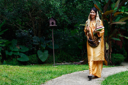 traditional clothing: Woman in traditional clothing walking with books in hand