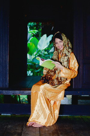 traditional clothing: Woman in traditional clothing reading book LANG_EVOIMAGES
