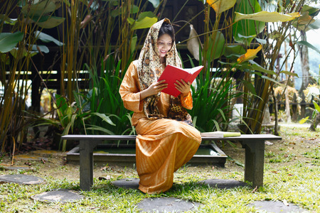 compound: Woman in traditional clothing reading book in the house compound LANG_EVOIMAGES