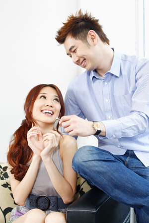 Receiving: Woman receiving a surprise gift from her boyfriend LANG_EVOIMAGES