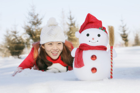 lying forward: Woman in warm clothing lying on snow and looking at snowman