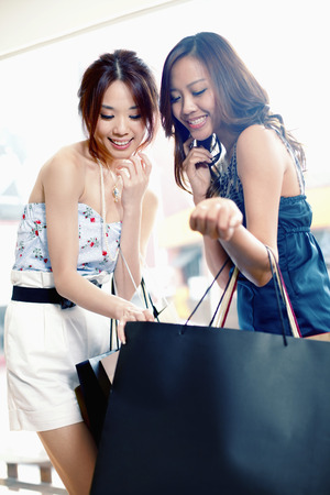looking inside: Women smiling while looking inside a shopping bag