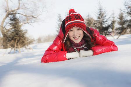 lying forward: Woman in warm clothing lying forward on snow