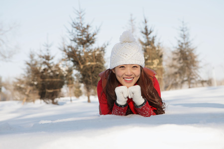 warm clothing: Woman in warm clothing lying on snow LANG_EVOIMAGES