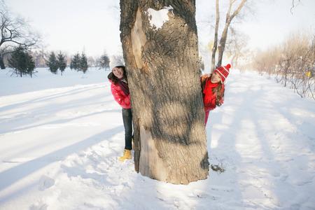 peeking: Women peeking from behind a tree