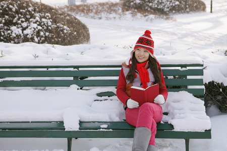 warm clothing: Woman in warm clothing reading book on a snowy bench