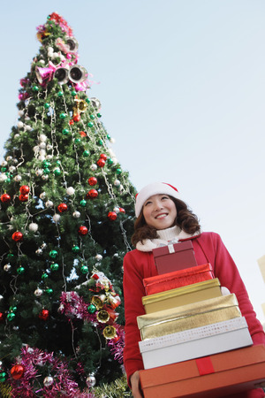 santa suit: Woman in Santa suit holding a stack of gift boxes
