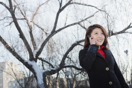 warm clothing: Woman in warm clothing talking on the mobile phone LANG_EVOIMAGES