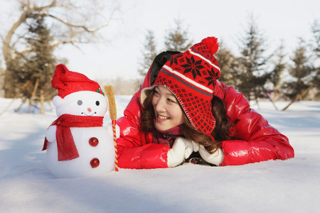 lying forward: Woman in warm clothing looking at snowman while lying forward on snow LANG_EVOIMAGES