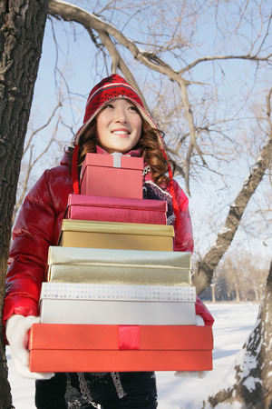 warm clothing: Woman in warm clothing with a stack of gift boxes  LANG_EVOIMAGES
