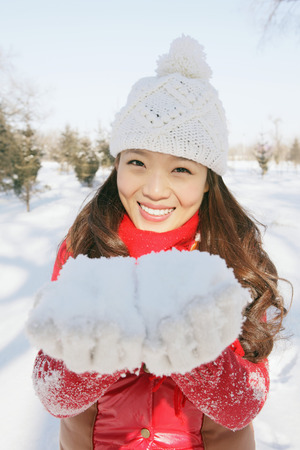 warm clothing: Woman in warm clothing playing with snow