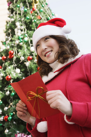 santa suit: Woman in Santa suit holding a greeting card