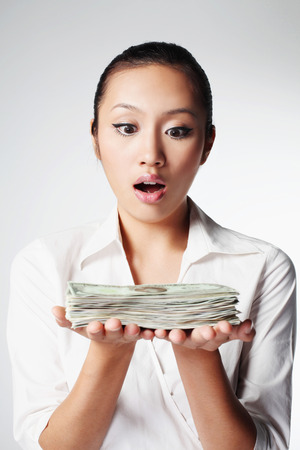 corporate greed: Businesswoman with a stack of money LANG_EVOIMAGES