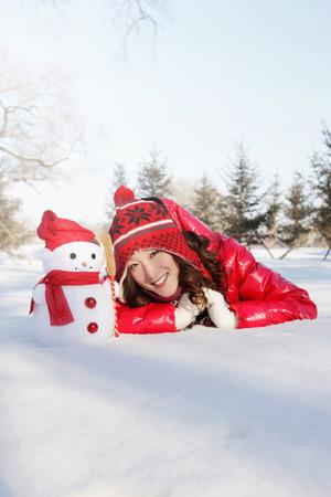 lying forward: Woman in warm clothing lying forward on snow with snowman