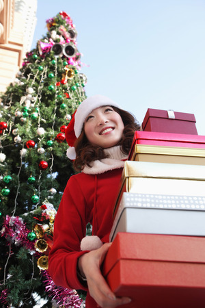 santa suit: Woman in Santa suit with a stack of gift boxes