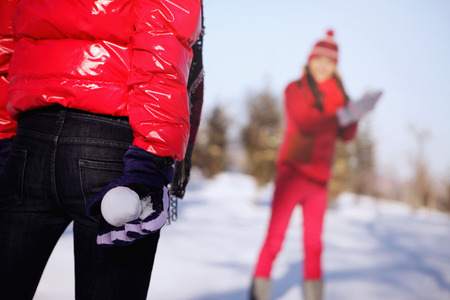 two people only: Woman hiding snowball behind her back