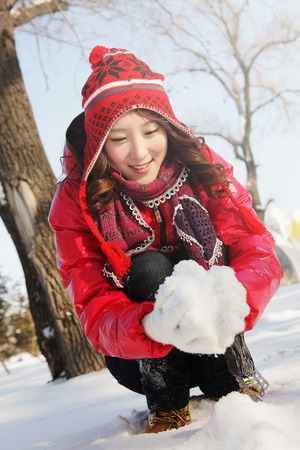 warm clothing: Woman in warm clothing making snowball