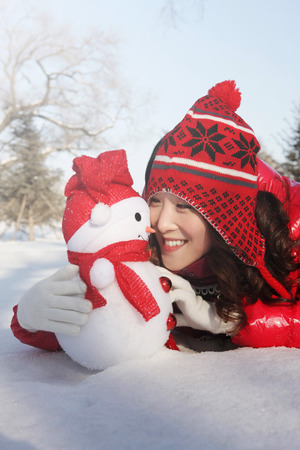 warm clothing: Woman in warm clothing looking at snowman while lying forward on snow LANG_EVOIMAGES
