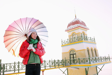 warm clothing: Woman in warm clothing holding an umbrella