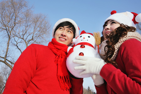 Man and woman posing with snowman