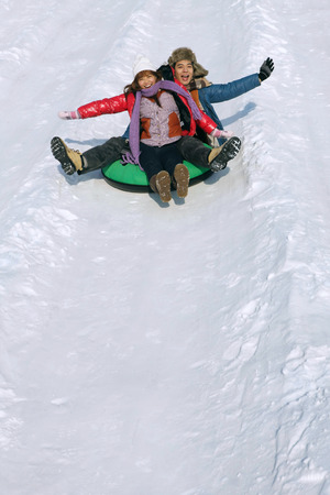 affectionate action: Man and woman sliding down snowy hill on inner tube