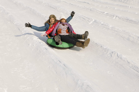 affectionate actions: Man and woman sliding down snowy hill on inner tube