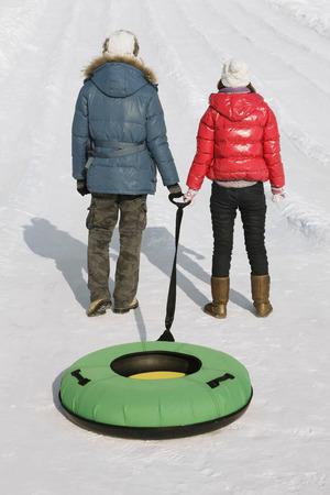 inner tube: Man and woman pulling inner tube LANG_EVOIMAGES