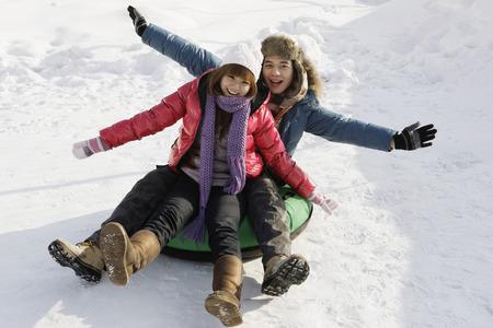 inner tube: Man and woman sliding down snowy hill on inner tube
