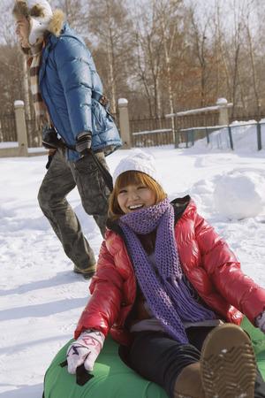 inner tube: Man pulling woman on inner tube