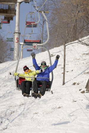 ski lift: Man and woman traveling on ski lift LANG_EVOIMAGES