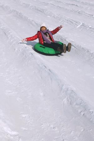 inner tube: Woman sliding down snowy hill on inner tube LANG_EVOIMAGES