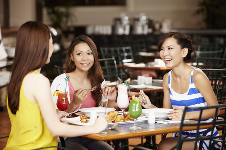Women chatting while having lunch together at restaurant Foto de archivo