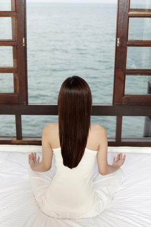 mujer meditando: Mujer meditando en la habitaci�n LANG_EVOIMAGES