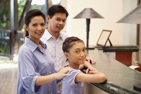 Girl with her parents at the hotel reception counter