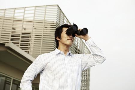 looking through an object: Businessman looking through binoculars